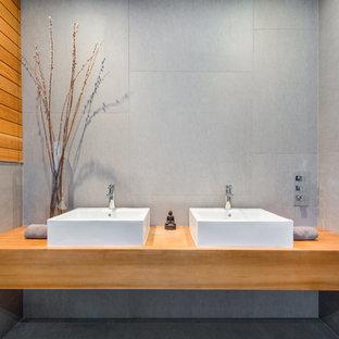 Diseño de sauna de estilo zen, pequeña, sin sin inodoro, con puertas de armario de madera oscura, sanitario de pared, baldosas y/o azulejos grises, baldosas y/o azulejos de porcelana, paredes grises, suelo de baldosas de porcelana, lavabo sobreencimera, encimera de madera, suelo verde y ducha abierta