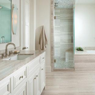 Foto de cuarto de baño clásico con lavabo bajoencimera, bañera encastrada sin remate, baldosas y/o azulejos beige, puertas de armario blancas, baldosas y/o azulejos de piedra caliza y encimeras grises
