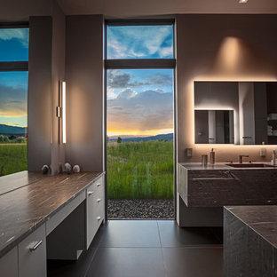 Esempio di una stanza da bagno padronale minimal di medie dimensioni con ante marroni, WC monopezzo, pareti grigie, pavimento in gres porcellanato, lavabo sottopiano, top in pietra calcarea, pavimento grigio e top marrone