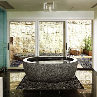 Inspiration for a mid-sized contemporary master black tile and stone tile porcelain floor and black floor bathroom remodel in Austin with white walls, a vessel sink, solid surface countertops, a wall-mount toilet and a hinged shower door