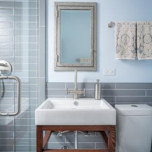 Modelo de cuarto de baño tradicional con armarios abiertos, sanitario de dos piezas, paredes azules y lavabo encastrado