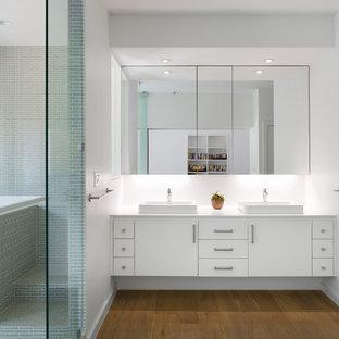 Immagine di una stanza da bagno padronale scandinava di medie dimensioni con lavabo a bacinella, ante lisce, ante bianche, top in quarzo composito, vasca giapponese, doccia a filo pavimento, piastrelle verdi, piastrelle di vetro, pareti bianche, pavimento in legno massello medio e pavimento marrone