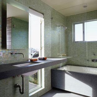 Idee per una stanza da bagno padronale moderna di medie dimensioni con vasca/doccia, piastrelle verdi, piastrelle di vetro, pareti verdi, pavimento in cemento, lavabo sottopiano, top in pietra calcarea e vasca sottopiano