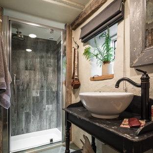 Modelo de cuarto de baño rústico, de tamaño medio, con ducha a ras de suelo, paredes beige, suelo de madera pintada, lavabo sobreencimera, suelo azul y ducha con puerta con bisagras