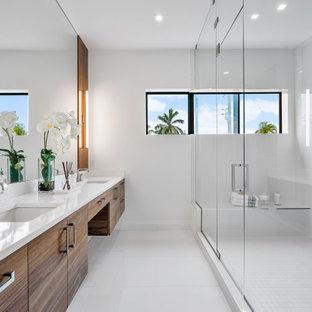 Inredning av ett modernt vit vitt badrum, med släta luckor, skåp i mörkt trä, en hörndusch, brun kakel, vita väggar, ett undermonterad handfat, vitt golv och dusch med gångjärnsdörr