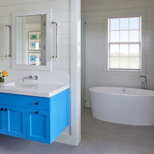 Ispirazione per una stanza da bagno padronale stile marino con ante in stile shaker, ante blu, vasca giapponese, doccia alcova, pareti bianche, pavimento in gres porcellanato, lavabo sottopiano, pavimento beige, porta doccia a battente e top bianco
