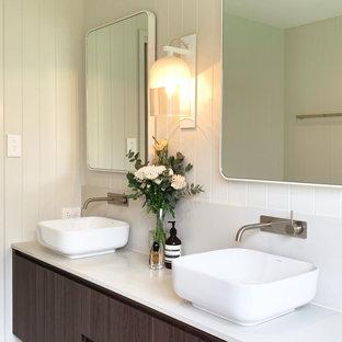На фото: со средним бюджетом главные ванные комнаты среднего размера с коричневыми фасадами, отдельно стоящей ванной, открытым душем, унитазом-моноблоком, серой плиткой, цементной плиткой, белыми стенами, полом из цементной плитки, настольной раковиной, столешницей из искусственного кварца, серым полом, открытым душем, белой столешницей, тумбой под две раковины, подвесной тумбой и панелями на части стены