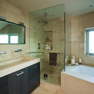 Modelo de cuarto de baño principal, actual, con armarios con paneles lisos, puertas de armario negras, bañera encastrada sin remate, ducha esquinera, paredes beige, suelo de piedra caliza y lavabo de seno grande