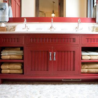 Modelo de cuarto de baño rústico, de tamaño medio, con lavabo bajoencimera, armarios con paneles empotrados, puertas de armario rojas, encimera de cuarzo compacto, baldosas y/o azulejos multicolor, suelo de baldosas tipo guijarro, paredes beige y suelo de baldosas tipo guijarro