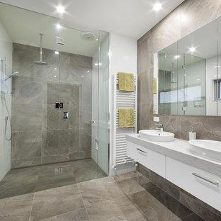 Esempio di una grande stanza da bagno padronale minimal con ante lisce, ante bianche, doccia a filo pavimento, pareti bianche, lavabo a bacinella, piastrelle grigie, porta doccia a battente, piastrelle in travertino, pavimento in travertino, top in marmo e pavimento grigio