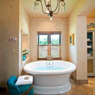 Foto de cuarto de baño rural, de tamaño medio, con armarios tipo vitrina, puertas de armario con efecto envejecido, bañera exenta, sanitario de pared, baldosas y/o azulejos negros, baldosas y/o azulejos de piedra, paredes beige y suelo de terrazo