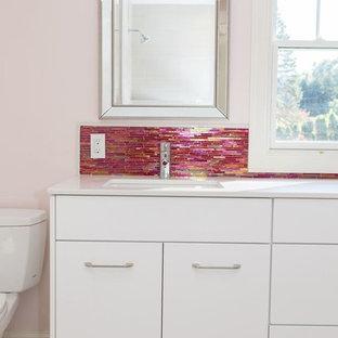 Foto di una stanza da bagno per bambini minimal di medie dimensioni con ante lisce, ante bianche, vasca ad alcova, doccia alcova, WC a due pezzi, piastrelle rosa, piastrelle di vetro, pareti rosa, pavimento in gres porcellanato, lavabo sottopiano e top in quarzite