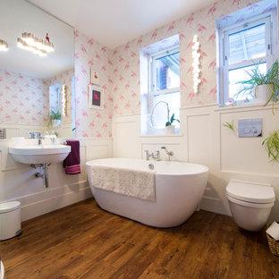 Ejemplo de cuarto de baño infantil, minimalista, de tamaño medio, con bañera exenta, ducha esquinera, sanitario de pared, baldosas y/o azulejos blancos, baldosas y/o azulejos en mosaico, paredes blancas, suelo laminado, lavabo suspendido, suelo marrón y ducha con puerta corredera