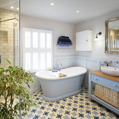 Bathroom - large coastal master beige tile and subway tile mosaic tile floor and blue floor bathroom idea in Sussex with raised-panel cabinets, blue cabinets, gray walls, wood countertops, a hinged shower door, a vessel sink and brown countertops