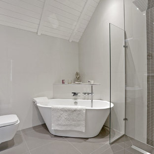 This is an example of a contemporary ensuite bathroom in Hertfordshire with a freestanding bath, a corner shower, grey tiles, grey walls, an integrated sink, grey floors and a hinged door.