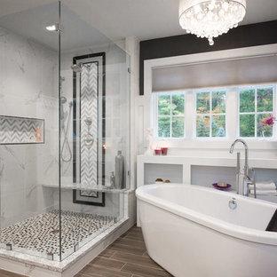 Klassisk inredning av ett stort en-suite badrum, med ett fristående badkar, en öppen dusch, vit kakel, stenkakel, svarta väggar, mörkt trägolv, ett undermonterad handfat och med dusch som är öppen