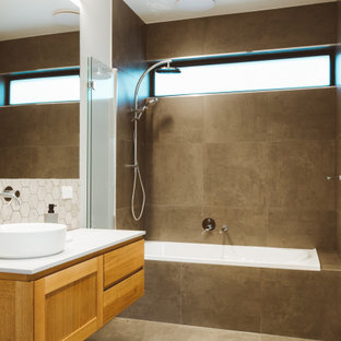 Mid-sized contemporary 3/4 bathroom in Hobart with shaker cabinets, medium wood cabinets, a drop-in tub, a shower/bathtub combo, gray tile, white walls, porcelain floors, a vessel sink, grey floor, a hinged shower door, white benchtops, a single vanity and a floating vanity.