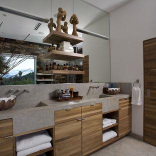 Imagen de cuarto de baño principal, minimalista, de tamaño medio, con lavabo integrado, armarios tipo mueble, puertas de armario de madera oscura, encimera de piedra caliza, baldosas y/o azulejos grises, losas de piedra y suelo de piedra caliza