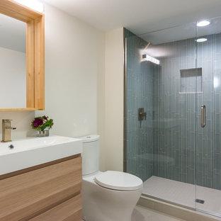 Foto di una piccola stanza da bagno con doccia minimalista con ante lisce, ante in legno chiaro, doccia alcova, piastrelle blu, piastrelle di vetro, pareti bianche, pavimento in gres porcellanato, lavabo integrato, top in quarzo composito e pavimento marrone