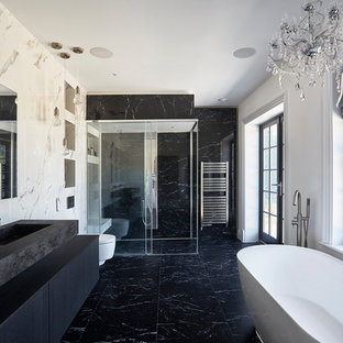 Design ideas for a contemporary shower room bathroom in Other with flat-panel cabinets, black cabinets, a freestanding bath, a built-in shower, a wall mounted toilet, white walls, an integrated sink, black floors, a sliding door and black worktops.