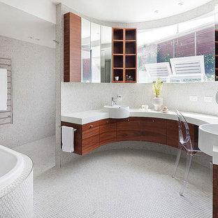 Idée de décoration pour une grand salle de bain principale design avec un placard à porte plane, des portes de placard en bois clair, un carrelage blanc, carrelage en mosaïque, un mur blanc, un sol en carrelage de terre cuite, une vasque, un plan de toilette en surface solide, une baignoire posée et un sol blanc.