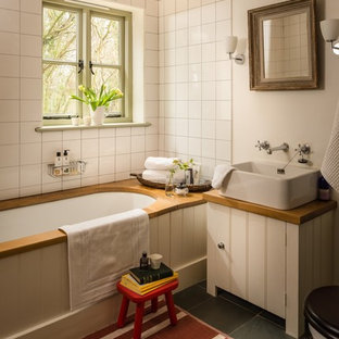 Medium sized rural family bathroom in Wiltshire with shaker cabinets, white cabinets, a built-in bath, a corner shower, a two-piece toilet, white tiles, ceramic tiles, white walls, slate flooring, a trough sink, wooden worktops, grey floors, a hinged door and brown worktops.