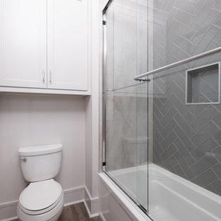 Foto di una piccola stanza da bagno con doccia chic con ante in stile shaker, ante bianche, pareti bianche, vasca ad alcova, vasca/doccia, WC a due pezzi, piastrelle grigie, piastrelle di vetro e porta doccia scorrevole
