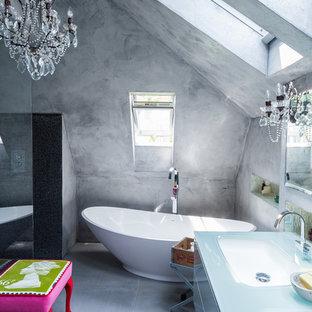 Ispirazione per una stanza da bagno padronale eclettica con lavabo sottopiano, top in vetro, vasca freestanding, doccia aperta, piastrelle nere, piastrelle a mosaico, pareti grigie, pavimento in cemento e doccia aperta