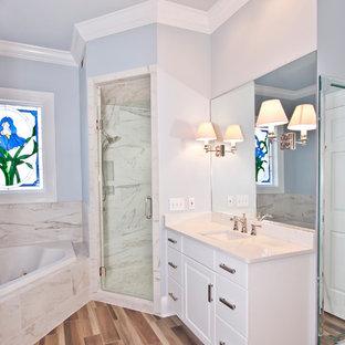 Großes Klassisches Badezimmer En Suite mit profilierten Schrankfronten, weißen Schränken, Eckbadewanne, Eckdusche, Wandtoilette mit Spülkasten, weißen Fliesen, Porzellanfliesen, grauer Wandfarbe, braunem Holzboden, Unterbauwaschbecken, Quarzwerkstein-Waschtisch, braunem Boden, Falttür-Duschabtrennung und weißer Waschtischplatte in Nashville