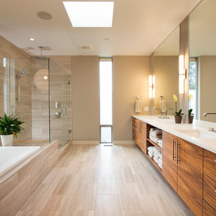 Photo of a contemporary bathroom in Vancouver with an undermount sink, flat-panel cabinets, a drop-in tub, a corner shower, beige tile, beige walls, medium wood cabinets and beige floor.