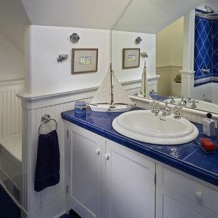 Immagine di una stanza da bagno stile marino con lavabo da incasso, ante con riquadro incassato, ante bianche, vasca/doccia, piastrelle blu, top piastrellato, pavimento blu e top blu