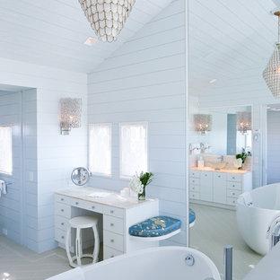 ボストンの小さいビーチスタイルのおしゃれなマスターバスルーム (置き型浴槽、フラットパネル扉のキャビネット、白いキャビネット、オニキスの洗面台、青い壁、トラバーチンの床) の写真