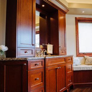 デンバーの巨大なトランジショナルスタイルのおしゃれなマスターバスルーム (レイズドパネル扉のキャビネット、茶色いキャビネット、ダブルシャワー、一体型トイレ、ベージュのタイル、磁器タイル、ベージュの壁、磁器タイルの床、アンダーカウンター洗面器、クオーツストーンの洗面台、茶色い床、開き戸のシャワー) の写真
