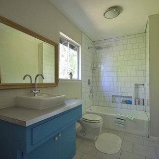 Immagine di una stanza da bagno padronale minimalista di medie dimensioni con lavabo a bacinella, consolle stile comò, ante marroni, top in laminato, vasca da incasso, doccia aperta, WC a due pezzi, piastrelle bianche, piastrelle in ceramica, pareti grigie e pavimento in gres porcellanato