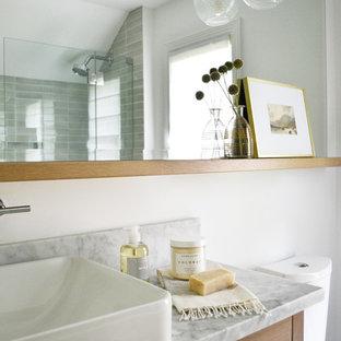 Mittelgroßes Klassisches Badezimmer En Suite mit flächenbündigen Schrankfronten, hellbraunen Holzschränken, Eckbadewanne, Duschbadewanne, Toilette mit Aufsatzspülkasten, grünen Fliesen, weißer Wandfarbe, Marmorboden, Aufsatzwaschbecken, Marmor-Waschbecken/Waschtisch, weißem Boden, Falttür-Duschabtrennung und grauer Waschtischplatte in Bridgeport