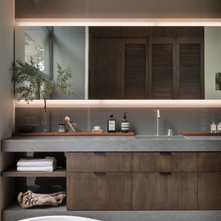 1960s master bathroom photo in Orange County with flat-panel cabinets, gray walls, an integrated sink, gray countertops and dark wood cabinets