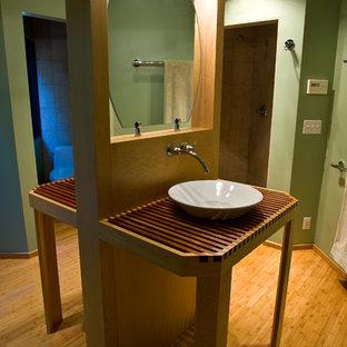 Imagen de cuarto de baño con ducha, rural, pequeño, con armarios abiertos, puertas de armario de madera clara, sanitario de una pieza, paredes verdes, suelo de bambú, lavabo sobreencimera, encimera de madera, suelo marrón y encimeras marrones