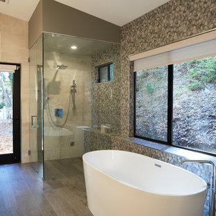 Bild på ett mellanstort funkis gul gult en-suite badrum, med släta luckor, vita skåp, ett fristående badkar, en vägghängd toalettstol, grön kakel, porslinskakel, gröna väggar, ljust trägolv, ett fristående handfat, marmorbänkskiva, en hörndusch, beiget golv och dusch med gångjärnsdörr