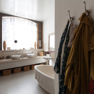 Freestanding bathtub - mid-sized eclectic master painted wood floor freestanding bathtub idea in London with marble countertops and white walls
