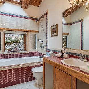 Modelo de cuarto de baño rural, de tamaño medio, con suelo de baldosas de cerámica, suelo blanco, armarios con paneles lisos, puertas de armario de madera oscura, bañera encastrada, combinación de ducha y bañera, sanitario de dos piezas, paredes blancas, lavabo encastrado, encimera de azulejos y encimeras rojas