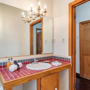 Ejemplo de cuarto de baño rural, de tamaño medio, con armarios con paneles lisos, puertas de armario de madera oscura, bañera encastrada, combinación de ducha y bañera, sanitario de dos piezas, paredes blancas, suelo de baldosas de cerámica, lavabo encastrado, encimera de azulejos, suelo blanco y encimeras rojas