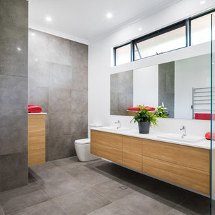 Photo of a contemporary bathroom in Perth with flat-panel cabinets, medium wood cabinets, engineered quartz benchtops, a one-piece toilet, gray tile, white walls, a vessel sink and white benchtops.