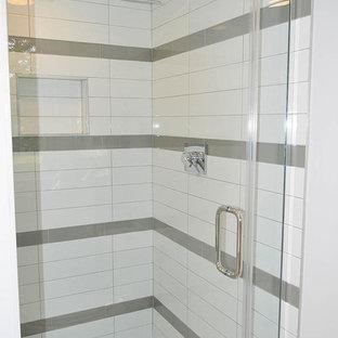 Modelo de cuarto de baño principal, minimalista, de tamaño medio, con lavabo suspendido, armarios con paneles lisos, puertas de armario grises, encimera de ónix, ducha doble, sanitario de dos piezas, baldosas y/o azulejos grises, baldosas y/o azulejos de cerámica, paredes grises y suelo de baldosas de cerámica