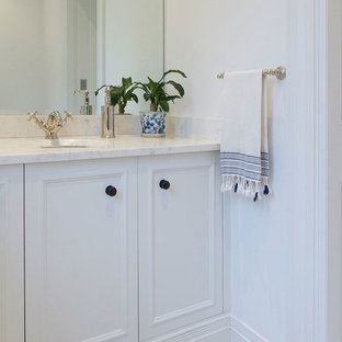 This is an example of a large country 3/4 bathroom in Sydney with recessed-panel cabinets, white cabinets, an open shower, white tile, ceramic tile, white walls, marble benchtops, a two-piece toilet, marble floors and an undermount sink.