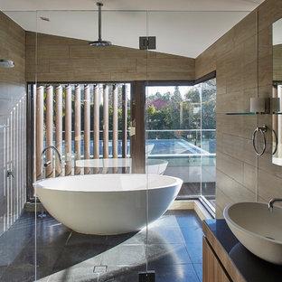 Bild på ett funkis svart svart en-suite badrum, med släta luckor, skåp i mellenmörkt trä, ett fristående badkar, våtrum, brun kakel, bruna väggar, ett fristående handfat, svart golv och dusch med gångjärnsdörr
