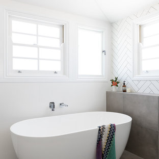This is an example of a large contemporary master bathroom in Brisbane with shaker cabinets, black cabinets, a freestanding tub, an open shower, a one-piece toilet, black tile, cement tile, white walls, cement tiles, an integrated sink, engineered quartz benchtops, grey floor, an open shower and white benchtops.