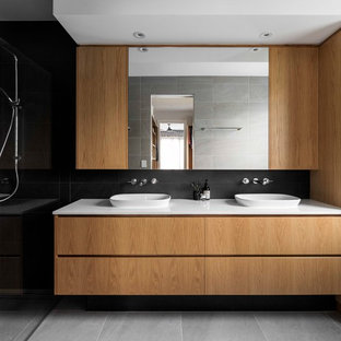 Large contemporary master bathroom in Brisbane with medium wood cabinets, black tile, white benchtops, flat-panel cabinets, a curbless shower, black walls, a vessel sink and grey floor.