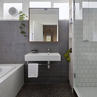 Inspiration for a contemporary bathroom in Melbourne with a drop-in tub, an alcove shower, blue tile, white tile, mosaic tile, white walls, a wall-mount sink, black floor and a hinged shower door.