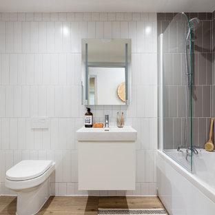 Стильный дизайн: ванная комната в стиле модернизм с плоскими фасадами, белыми фасадами, накладной ванной, душем над ванной, унитазом-моноблоком, серой плиткой, керамической плиткой, белыми стенами, полом из ламината, накладной раковиной и душем с распашными дверями - последний тренд