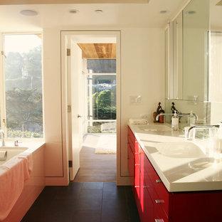 Imagen de cuarto de baño principal, moderno, extra grande, con puertas de armario de madera oscura, bañera encastrada, paredes blancas, lavabo encastrado, suelo gris y encimeras rojas